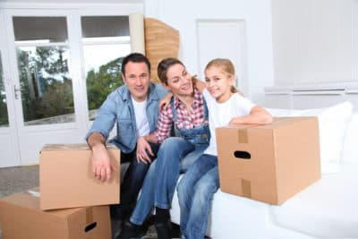 Bilde av en mann og dame med et barn som sitter på sengen og har tre flytteesker