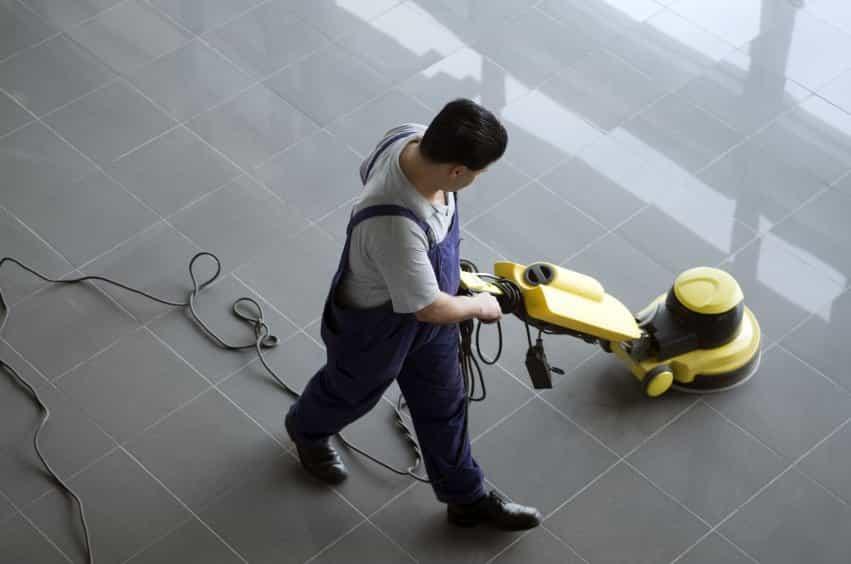 Mann som vasker gulvet for en bedrift med en maskin som vasker gulvet